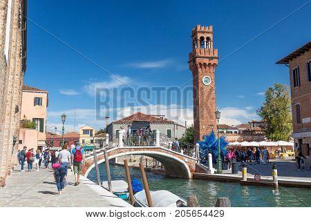 MURANO, ITALY - SEPTEMBER, 2017: Murano, Venice Italy in the summer season. Bridge with canal and Murano campanile