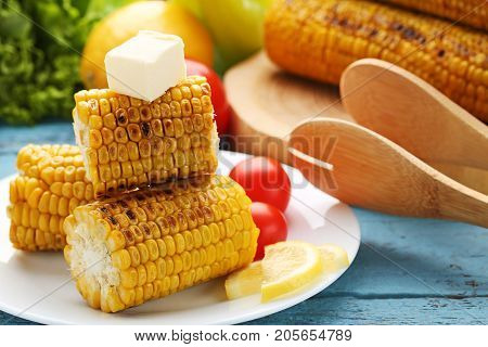 Tasty Grilled Corns With Butter And Tomatoes On Blue Wooden Table