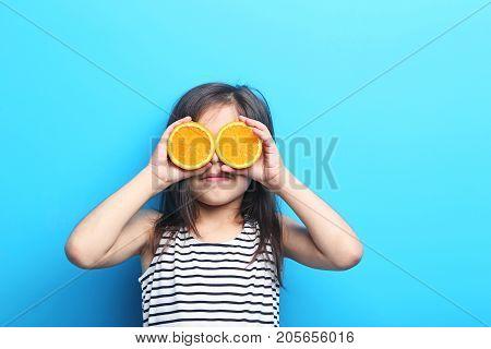 Beautiful Little Girl With Orange On Blue Background