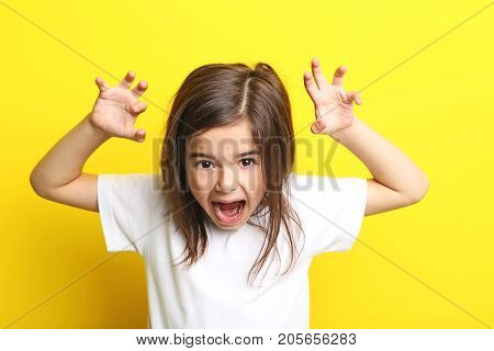 Beautiful little girl on the yellow background
