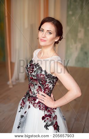 Beautiful luxurious female model with medium brown hair in a long fashinable dress standing in the room. Bridal clothes concept. Stylish wedding dress.