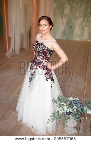 Full-length shot of a beautiful woman with makeup and elegant hairstyle. Bridal clothes concept. Stylish wedding dress.