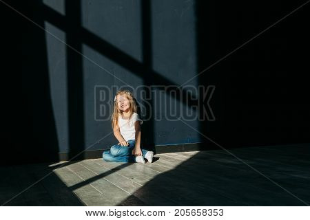 Happy little girl portrait siting on gray background wooden floor room window sunny day