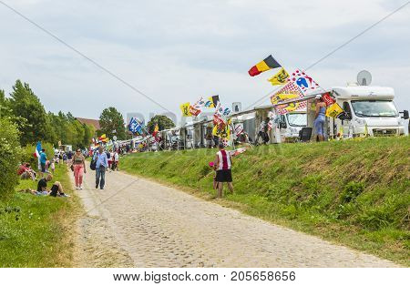 QuievyFrance - July 07 2015:Spectators and caravans are on the cobblestone road during the stage 4 of Le Tour de France 2015 in Quievy France on 07 July2015.