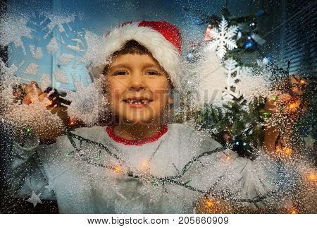Looking through frosty cold window little boy in santa hat near the Christmas tree and illumination