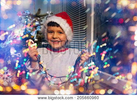 Nice little boy with garland of Christmas lights in Santa hat in living room