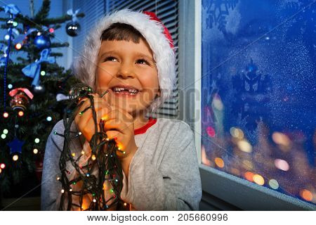 Happy little boy laughing smiling and holding New Year illumination lights about to put them on Christmas tree
