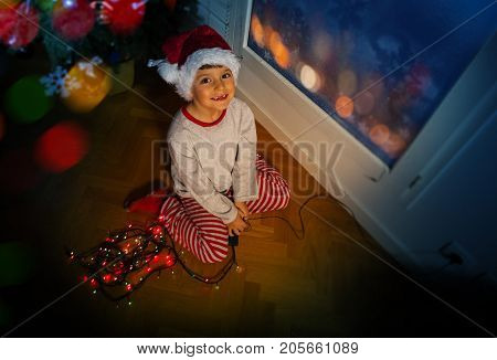 Nice little boy sitting on the floor near Christmas tree with garland and in Santa hat during night smiling