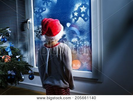 Small boy in Santa hat standing in front of the frosty winter New Year window looking at night waiting for Christmas