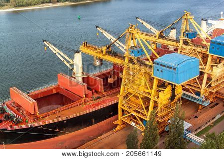 Crane unloads iron ore at the harbor. Trade in raw materials. Work at a port in the Baltic Sea