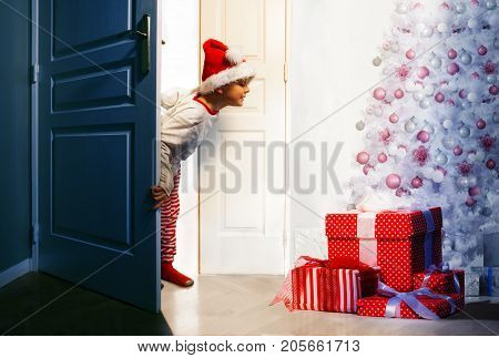 Little curious handsome boy checks presents under Christmas tree looking from the door  in the night