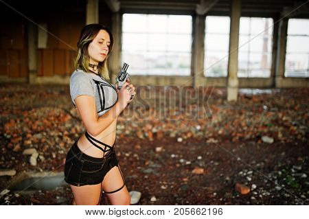 Girl wear on shorts and black erotic fetish underwear with gun at had on abadoned factoty with brick. poster