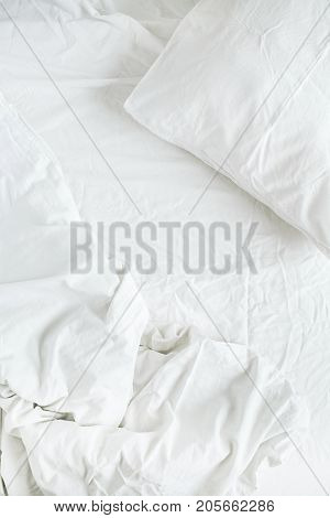 Flat lay of white bed with pillows blanket and sheet. Top view minimal linen concept.