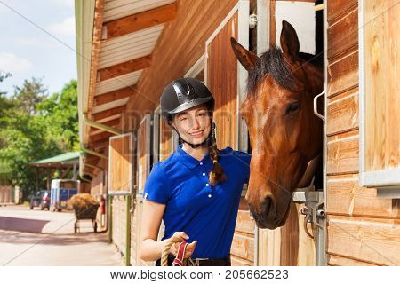 Portrait of happy jockey girl standing with her bay horse by riding stables in summer