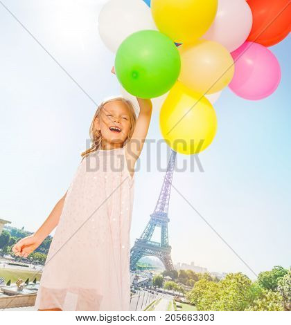 Portrait of happy little girl playing with colorful balloons bouquet against the Eiffel Tower at sunny day