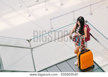 Cute teenage Asian traveler girl college student using smartphone call or chat at airport with luggage backpack. Web check in lonely travel study abroad or international tourism lifestyle concept.