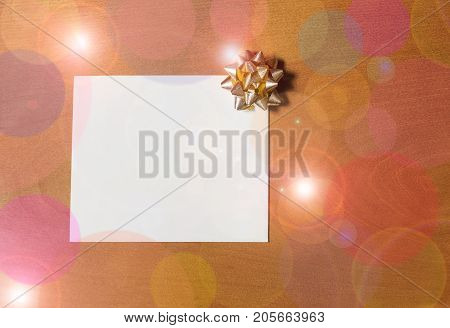 Note card with golden bow on wooden background