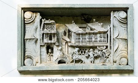 Shanghai, China - Nov 4, 2016: Gucheng Park (Northeast Gate) - A decorative concrete inset in the gate wall depicting daily life in ancient times. A three-dimensional scene.