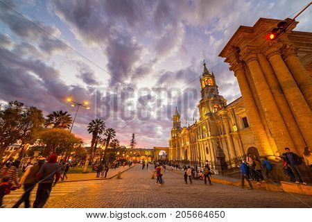 Arequipa Peru - August 16 2015: People roaming in Plaza de Armas in front of the Cathedral of Arequipa at dusk. Wide angle view from below with scenic colorful sky and clouds.
