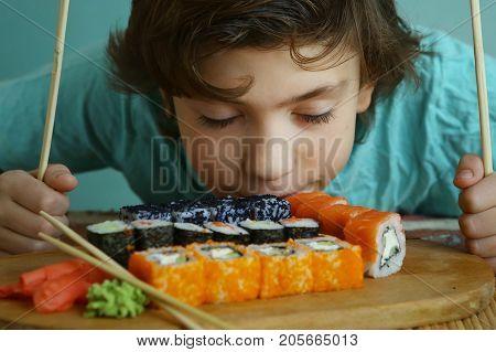 Teenager Boy Eating Sushi Rolls Set With Japanese Sticks