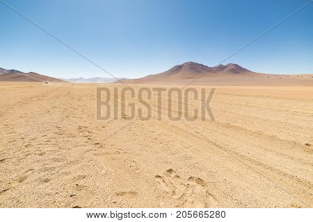 Dirt Road At High Altitude With Sandy Desert And Barren Volcano Range On The Andean Highlands. Road