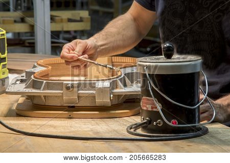 Craftsman Working On Wooden Acoutstic Guitar