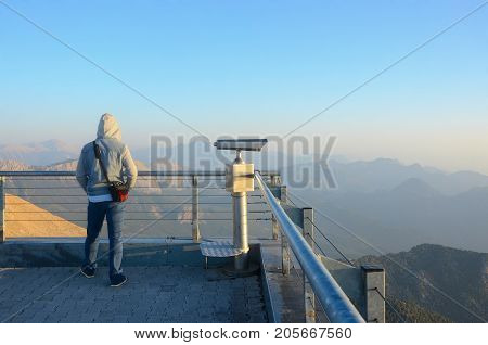 A young man watches sunrise in the mountains. Dawn in the mountains. Telescope on the observation deck on top of the mountain.