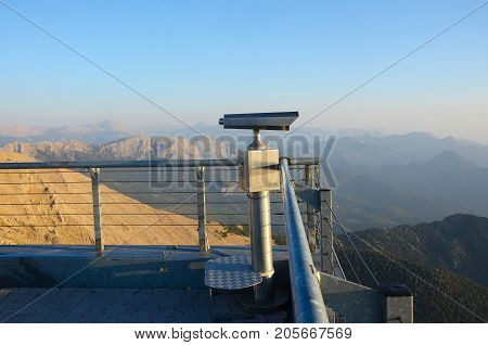 Dawn in the mountains. Telescope on the observation deck on top of the mountain.