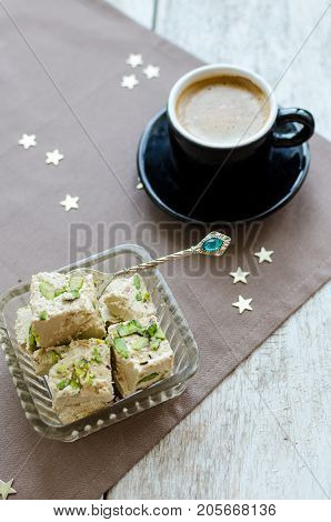 Traditional eastern dessert - halva pistachio and cup of coffee. Arabian sweets on wooden table. Turkish delight concept. poster