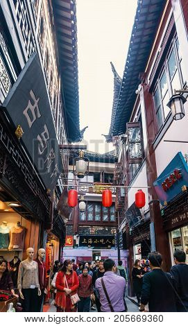 Shanghai, China - Nov 4, 2016: On Yu Yuan Old Steet - Area bustling with people. The building is constructed in classical or traditional Chinese architectural design. Red lanterns hanging above.