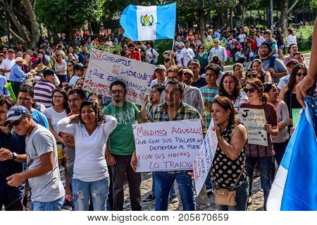 Antigua Guatemala - September 15 2017: Locals wave Guatemalan flags & slogans protesting against government corruption in front of city hall on Guatemala's Independence Day.