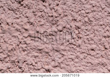 The rough texture of the decorative plaster on the wall. The surface of pink or beige with drips drops and cracks. There are dimples and bumps.