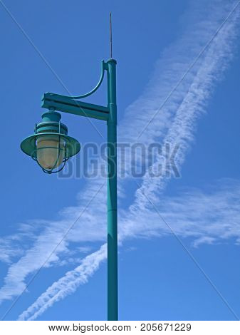 A colorful lamppost rises into a blue sky streaked with just a few white clouds. It is a lovely summer day.