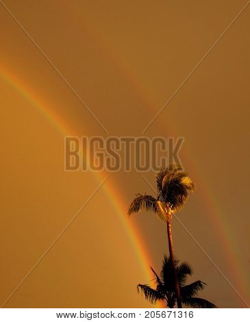 A glowing warm sunset after a storm produced a double rainbow in Maui.