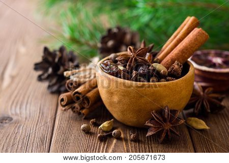 Set Of Spices For Mulled Wine In Ceramic Bowl On Wooden Table.
