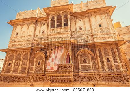 Old city house with carvings on balcony and walls. Indian tradition of architecture.