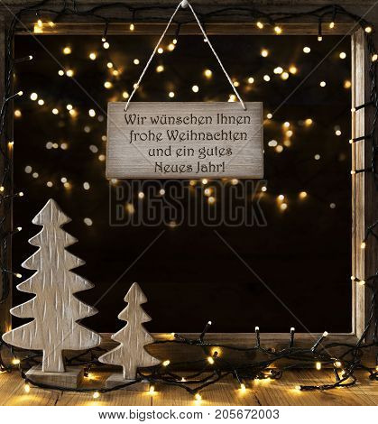 Sign With German Text Wir Wuenschen Ihnen Frohe Weihnachten Und ein Gutes Neue Jahr Means We Wish You A Merry Christmas And A Happy New Year. . Window Frame With Christmas Tree And Fairy Lights.