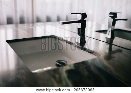 Modern tap faucet and sink on new bathroom