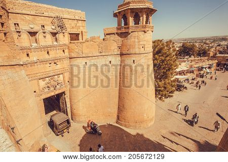 JAISALMER, INDIA - Feb 1, 2016: People going to gates of historical Jaisalmer fort with stone towers in Thar desert on February 1, 2016. Jaisalmer has a population of about 78000.
