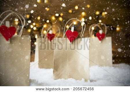 Christmas Shopping Bags On Snow. Bright Glowing Romantic Lights In Background And Snowflakes. Paper Bags With Copy Space And Red Hearts