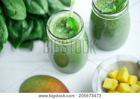 Mango with Banana and Spinach smoothie on white wooden table.