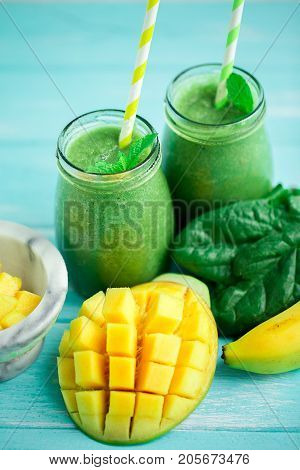 Mango with Banana and Spinach smoothie on blue wooden table.