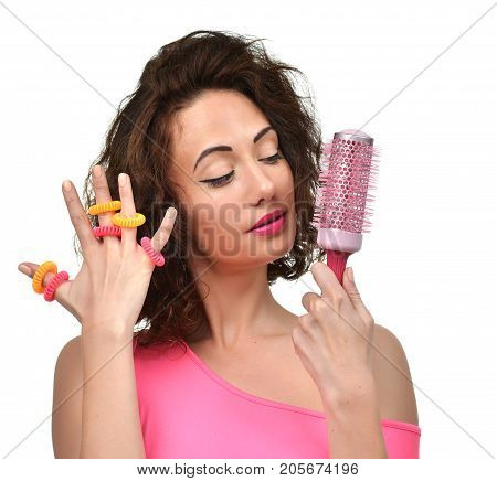 Closeup portrait of happy fashion brunette woman with big pink hair brush and scrunchy looking at the corner isolated on a white background