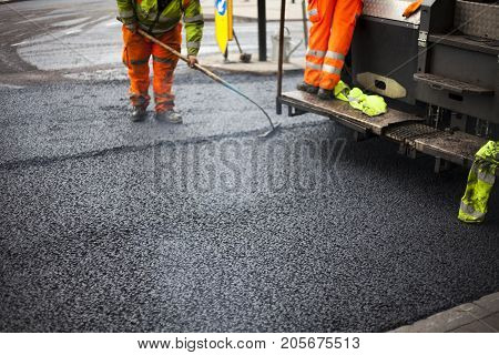 A roadworks on the street new asphalt with workers, Road Roller Road Construction Machinery.
