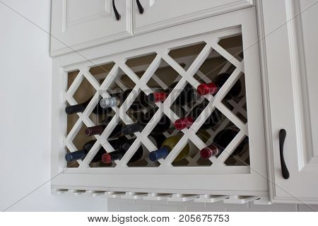 White colored built-in wine rack kitchen cabinets.