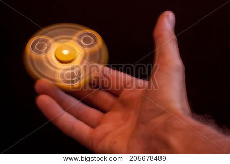Yellow spinner spinning in the hands of a teen toy to relieve stress and calm the nerves of the sick