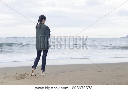 Young Pretty Woman Standing Alone On The Beach Near The Sea.