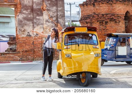 Traveler japanese girl hollding map travel query for the way with old man driver taxi or tuk tuk touring Ayutthaya Province Thailand