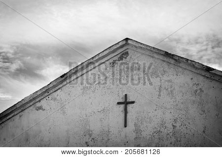 Black and white photo of the cross on the roof of the church