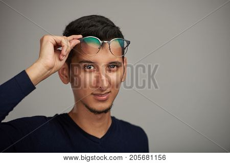 Young man with glasses on forehead isolated on gray background